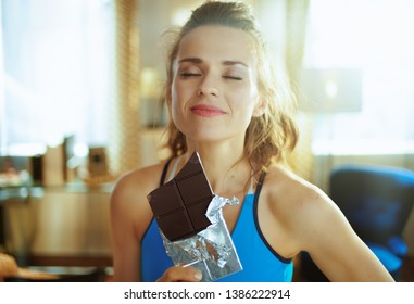 Portrait of smiling active sports woman in sport clothes in the modern house enjoying chocolate bar.