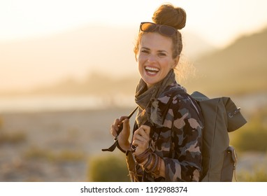 Portrait of smiling active tourist woman in hiking clothes against mountain and sea landscape at sunset