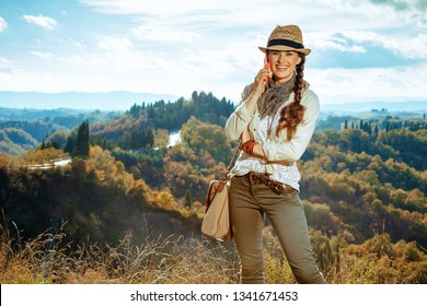 Portrait of smiling adventure tourist woman in hiking gear with bag in the front of scenery of summer Tuscany ,Italy talking on a cell phone.