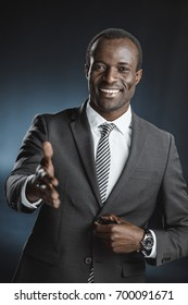 portrait of smiling african american businessman with outstretched hand looking at camera isolated on black