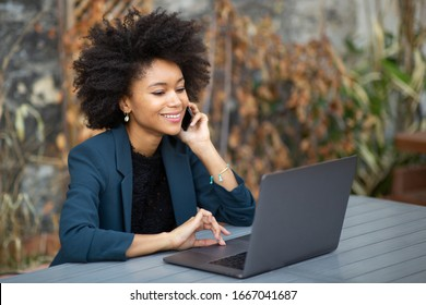 Portrait smiling african american businesswoman using laptop computer and talking with cellphone