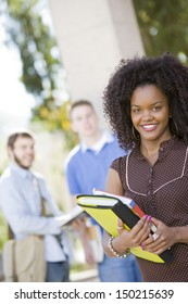 Portrait of smiling African American female student on college campus with classmates in background