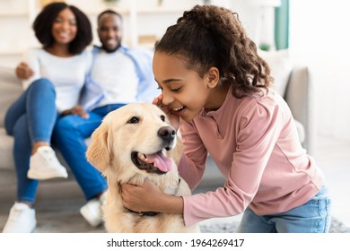 Portrait of smiling African American girl whispering something in the ear to her pet, telling secret and emracing happy dog, spending time together with best friend in living room, selective focus