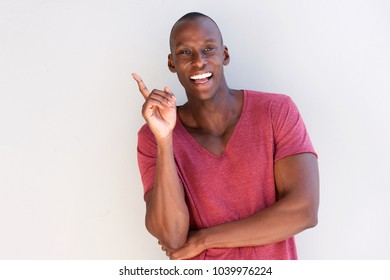 Portrait of smiling african american man pointing finger by white wall