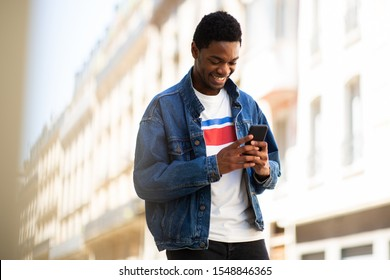 Portrait of smiling african american man looking at cellphone in city