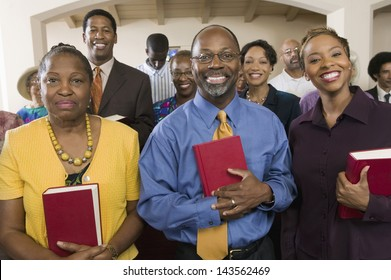 Portrait of smiling African American people standing with bibles in the church