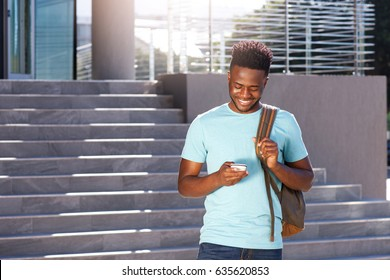 Portrait of smiling african american student looking at cellphone