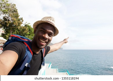 Portrait of smiling african american travel man taking selfie by the sea and pointing finger