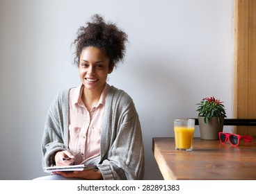 Portrait of a smiling african american woman sitting at home with pen and paper