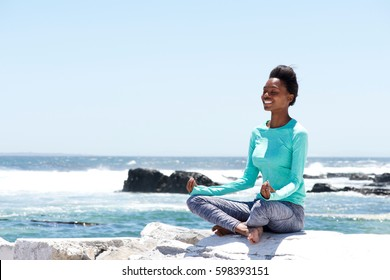 Portrait of smiling african american woman doing yoga by the sea