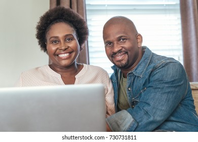 Portrait of a smiling African couple browsing online with a laptop while sitting and relaxing together on their living room sofa at home