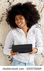 Portrait of smiling african girl lying on floor with digital tablet