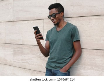 Portrait smiling african man with phone wearing t-shirt, sunglasses on city street over gray wall background