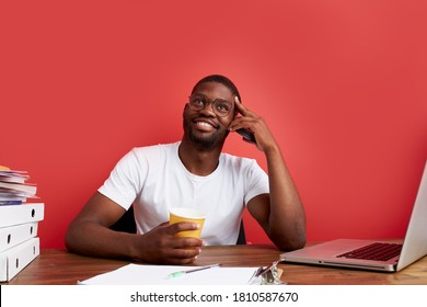 portrait of smiling african man sitting at office desk, drinking cup of coffee in the morning, isolated over red background