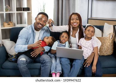 Portrait of smiling african parents with their three kids holding keys from new house. Happy family sitting on couch with modern laptop among many boxes.