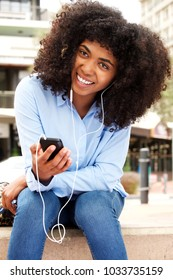 Portrait of smiling african woman sitting outside with smart phone and earphones