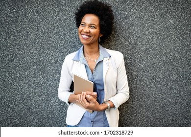 Portrait of smiling african woman walking in the city with tablet