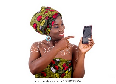 Portrait of a smiling african young woman in african cloth with drawing tinted body. she holds and shows a mobile phone on background