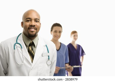 Portrait of smiling African-American man and Caucasian women medical healthcare workers in uniforms standing against white background.