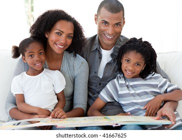 Portrait of a smiling Afro-American family reading a book in the living-room