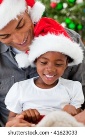 Portrait of a smiling Afro-American father and daughter playing with Christmas gifts