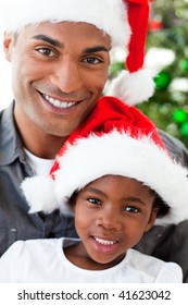 Portrait of a smiling Afro-American father and daughter at Christmas time