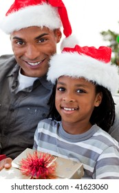 Portrait of a smiling Afro-American father and son holding a Christmas gift