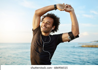 Portrait of a smiling afro-american sports man stretching his muscular arms before workout by the sea, using music app on his smartphone. Dark-skinned athlete warming up before running.
