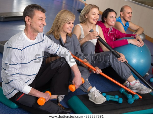 Portrait of smiling aged men and women in top form in modern gym