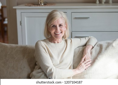 Portrait of smiling aged woman sit on cozy couch relaxing posing for picture, happy energetic senior female rest on comfortable sofa at home, elderly lady look at camera making photo in country house