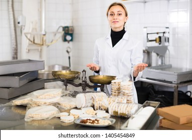 Portrait of smiling american female with packing of turron in food factory