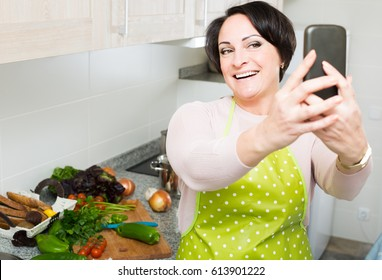 Portrait of smiling american  housewife in apron making selfie in domestic kitchen