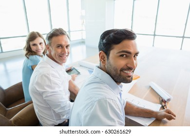 Portrait of smiling architects sitting together in office