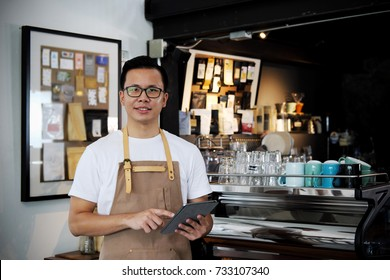 Portrait of smiling asian barista holding digital tablet at counter in coffee shop. Cafe restaurant service, Small business owner, food and drink industry concept.