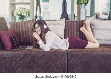 Portrait of smiling asian beautiful young businesswoman listening the music with Earphone in the modern living room, lifestyle concept
