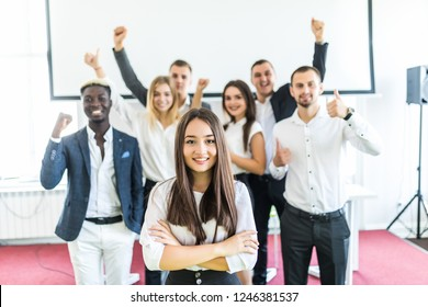 Portrait of smiling asian businesswoman in front of diverse business team.