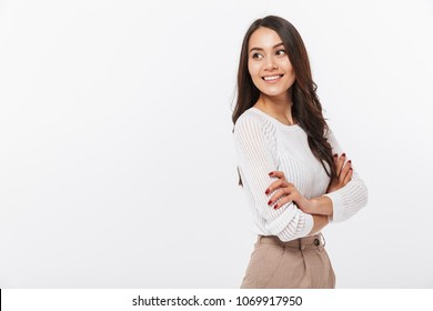 Portrait of a smiling asian businesswoman standing with arms folded and looking away isolated over white background
