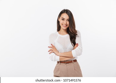 Portrait of a smiling asian businesswoman standing with arms folded and looking at camera isolated over white background
