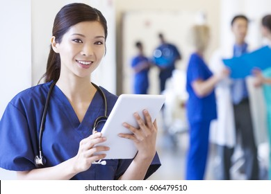 Portrait smiling Asian Chinese female clinical hospital nurse in scrubs using wireless tablet at modern medical center