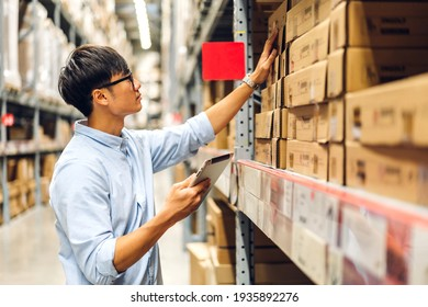 Portrait of smiling asian engineer foreman in helmets man order details checking goods and supplies on shelves with goods background in warehouse.logistic and business export