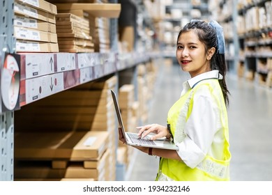 Portrait of smiling asian engineer woman check stock details on tablet computer for checking boxes with logistics on shelves with goods background in warehouse, logistic and business export