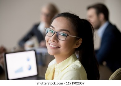 Portrait of smiling Asian female employee looking at camera during office business meeting, happy woman worker posing shooting at briefing, making professional picture in boardroom