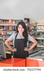 Portrait of smiling asian female staff standing at cash counter in supermarket