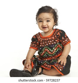 Portrait of a Smiling Asian Indian Baby Girl in Traditional Attire on White