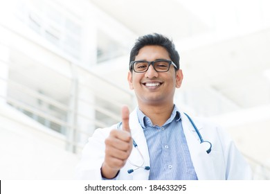 Portrait of a smiling Asian Indian male medical doctor in uniform thumb up, hospital building at background.