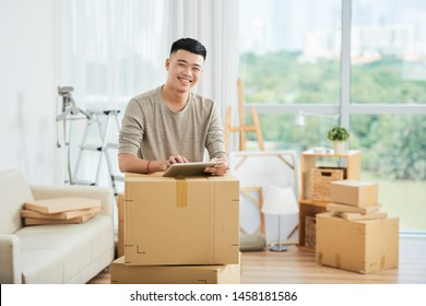Portrait of smiling Asian man standing near the packed boxes and using digital tablet he prepared boxes for delivery