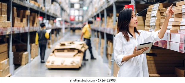 Portrait of smiling asian manager worker woman standing and order details on tablet computer for checking goods and supplies on shelves with goods background in warehouse.logistic and business export