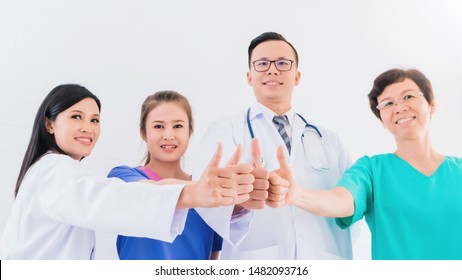 Portrait of smiling Asian medical male Doctor standing and showing hand thumb up with team staff in hospital background.Concept of effective work in hospitals.