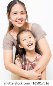 Portrait of a smiling Asian mother embracing the little daughter