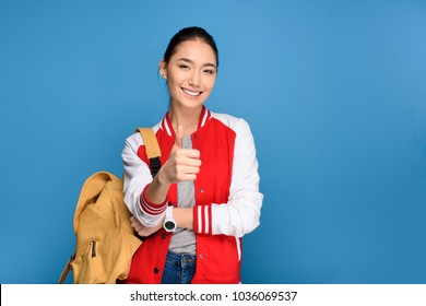 portrait of smiling asian student showing thumb up isolated on blue